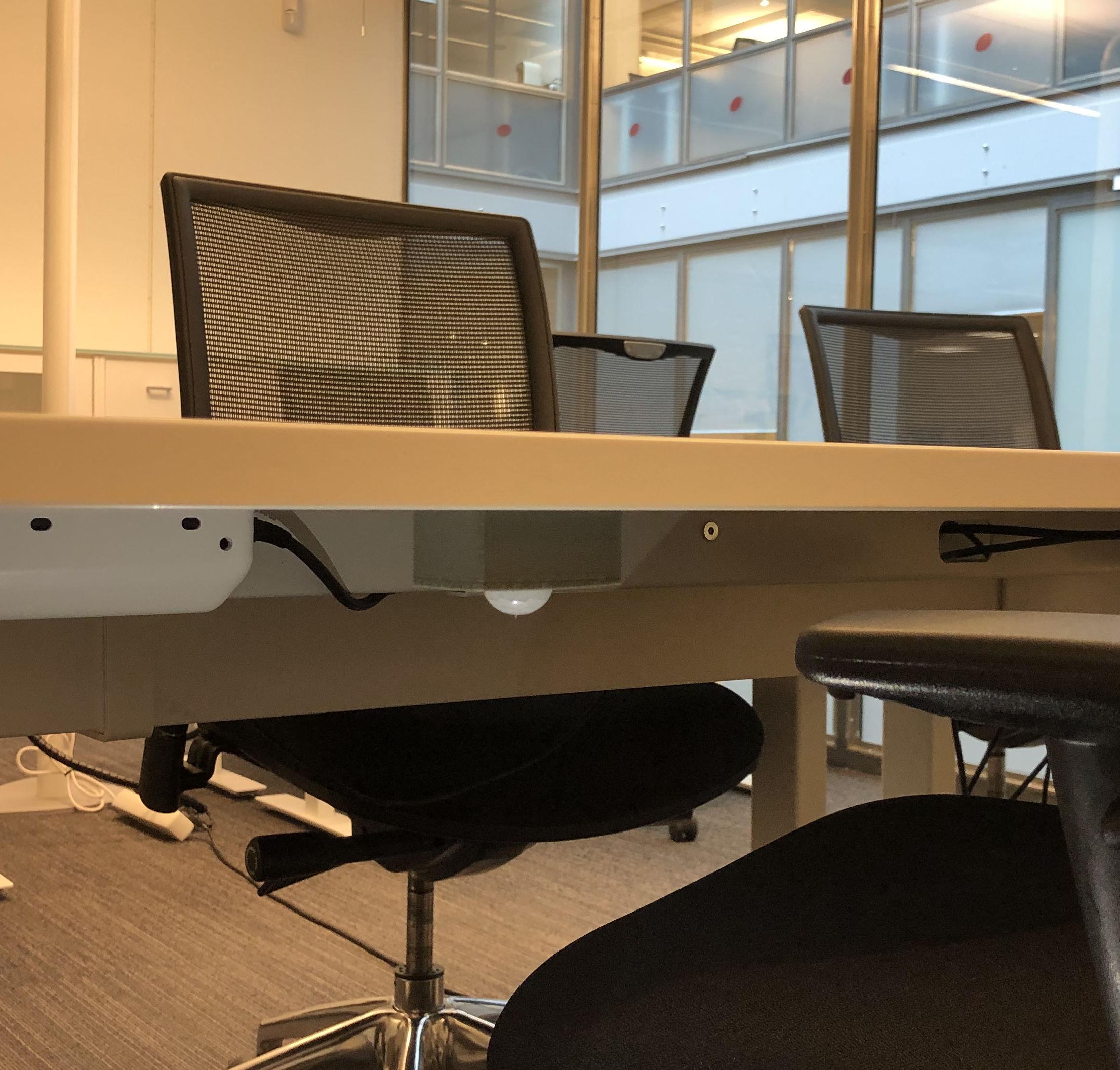 Capteur de présence de hot desk IoT sans fil installé sur un bureau dans un bureau